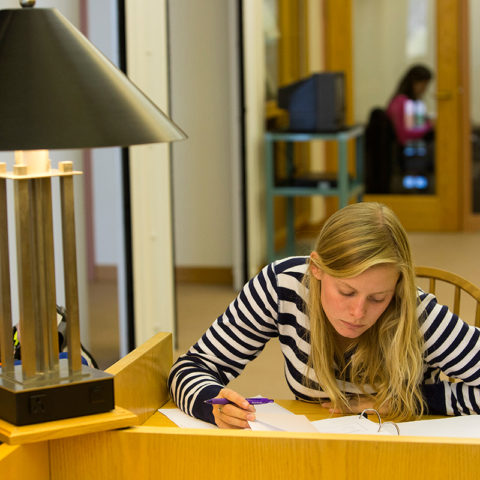 Clarke University Religisou Studies student studying in the library