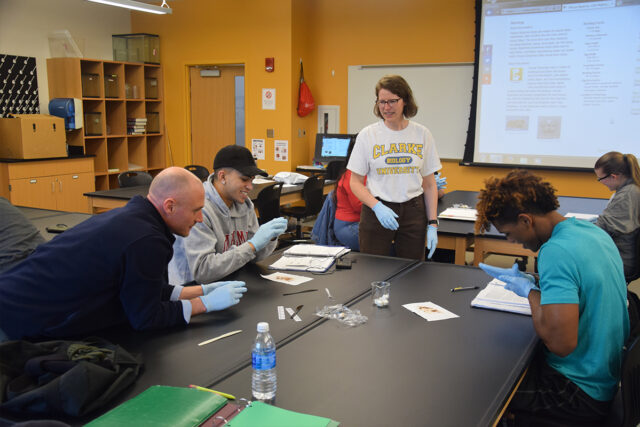 A biology professor works with undergrad biology students