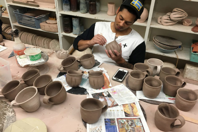Erik Brolin puts on the finishing touches to his ceramic mugs.