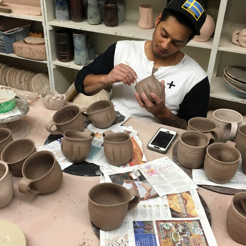 Erik Brolin puts on the finishing touches to his ceramic mugs.