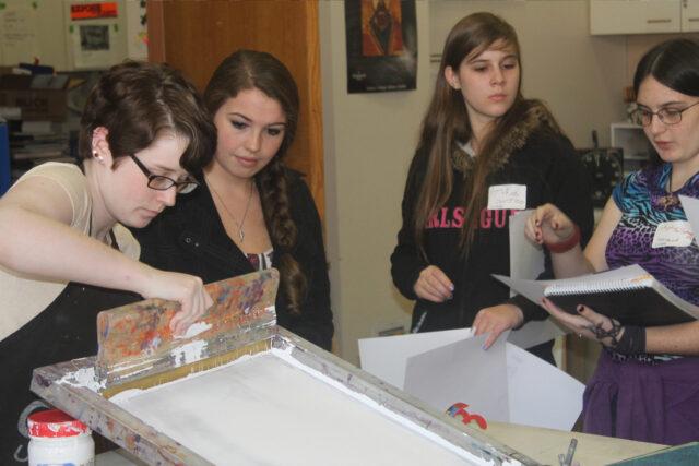 Students work on screen printers