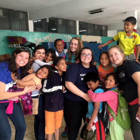 Clarke students with children while studying abroad in Equcador