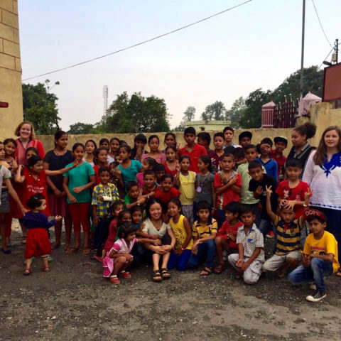 Clarke students with children while studying abroad in India